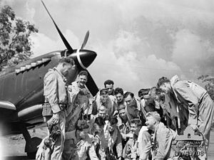 Strauss Airfield - Pilots of No. 452 Squadron RAAF being briefed by the Commanding Officer, Squadron Leader L. T. (Lou) Spence, circa December 1944 (right, kneeling)
