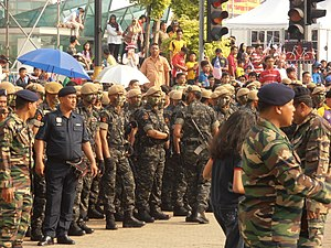 Pasukan Gerakan Khas - Several officers from 69 Commando of PGK standby to demonstrate the Gayung Perang war dances during the 56th National Day Parade of Malaysia at Merdeka Square, Kuala Lumpur. The officer on the right has a slung Colt M4A1 Carbine.