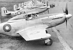 Row of a dozen or so single-engined fighters on an airfield