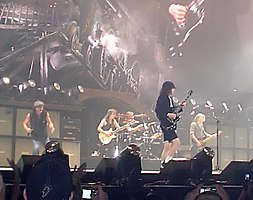 Rock band in performance on a well-lit but hazy stage. At the back is a guitarist; there are two more guitarists, a vocalist off to one side, and a drummer in the rear.