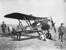 Biplane with soldiers wearing slouch hats standing around it.