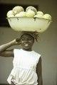 "ASC Leiden - F. van der Kraaij Collection - 01 - 082 - ""Martha"" A smiling young fruit saleswoman in a white blouse with a headscarf - Monrovia, Old Road, Montserrado County, Liberia, 1976.tiff"