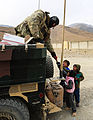 A U.S. Air Force pararescueman assigned to the Combined Joint Special Operations Task Force-Afghanistan gives treats to children in Kabul province, Afghanistan, Jan. 7, 2014 140107-A-CL980-047.jpg