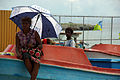 A woman sits on a boat with an umbrella at the small boat wharf in Honiara. (10664186844).jpg
