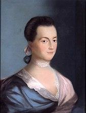 Mulher com cabelos pretos profundos e olhos escuros, usando um vestido azul e rosa