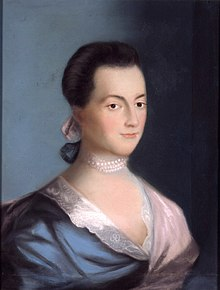 Woman with deep black hair and dark eyes wearing a blue and pink dress
