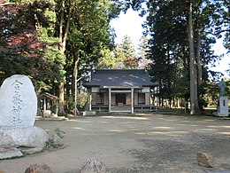 A small Shinto shrine surrounded by trees, with a stone tablet in the foreground