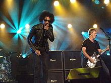 A banda Alice in Chains desempenho no palco uma palestra do programa de TV.  Um cantor masculino, William Duvall, canta em um microfone.  Um guitarrista do sexo masculino toca guitarra.