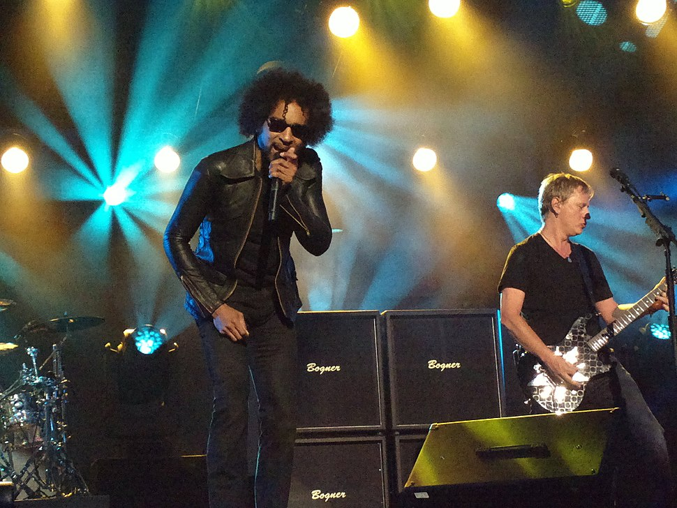 The band Alice in Chains performing on a TV talk show's stage. A male singer, William Duvall, sings into a microphone. A male guitarist plays electric guitar.