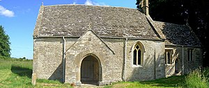 A very small stone church seen from the south with a prominent doorway, and a smaller chancel towards the right