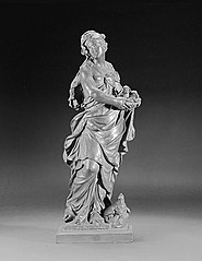 Fertility (?) Allegorical statue of a woman, standing, holding a basket containing two lambs, with a hen at her feet
