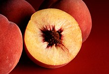 Photograph showing a peach in cross section with yellow flesh and a single large reddish brown pit
