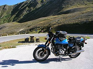 Blue BMW R65 motorcycle with tank bag, parked close to a bend in a mountain road
