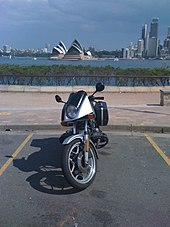 Front view of BMW R65LS motorcycle parked in a car park with the Sydney Opera House visible across the bay