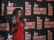 Beyoncé is smiling while standing in front of a black wall with several images of the 2009 MTV Video Music Awards logo on it. She wears a red dress and she is holding a silver astronaut-shaped trophy.