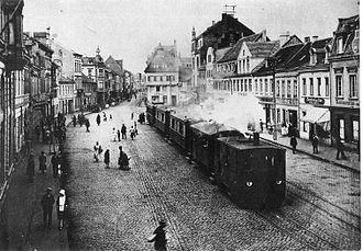 History of trams - A German steam tram engine from the Cologne-Bonn railway, pulling a train through Brühl marketplace, around 1900