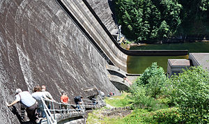 A group of people descend single-file down a long, steep stairway attached to the backside of a river dam.