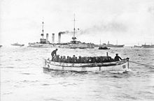 A small white boat filled with soldiers passes in front of a large warship with three tall funnels and several smaller transport ships.