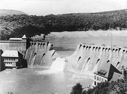 Dam with a V-shaped breach and water flooding through