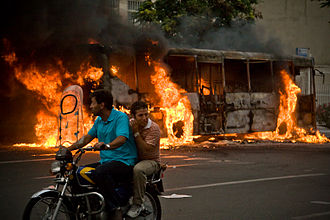 2009 Iranian presidential election protests - A bus burns on the streets of downtown Tehran as protesters cycle by on the 13 June
