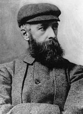 A portrait photograph of a bearded man in a plain hat and jacket