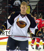 An ice hockey player stands directly upright holding an ice hockey stick horizontally across his stomach. He is wearing a no helmet and is wearing a black and white uniform with a large orange bird with an ice hockey stick on his chest.