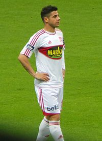 Cicinho on a football pitch, standing with his hands on his hips. He is wearing an all-white kit with red trim