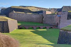 photographie montrant au premier plan la Porte de Brisach, les fortifications murs d'enceinte de la partie nord, à l'arrière-plan, la Tour des Bourgeois et la citadelle