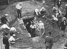 Black and white photo of men and women working on constructing an earthen mound with a doorway cut into it. The doorway is lined with sandbags.