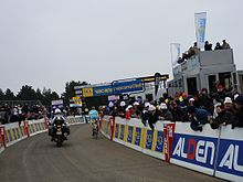 Many spectators in warm clothes stand behind barricades watching a lone cyclist in a blue and yellow jersey with white trim. A motorcycle follows the cyclist.