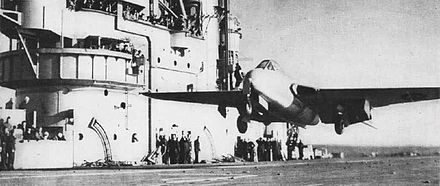 "The first carrier landing and take-off of a jet aircraft: Eric ""Winkle"" Brown landing on HMS Ocean in 1945 DeHavilland Vampire HMS Ocean Dec1945 NAN1 47.jpg"