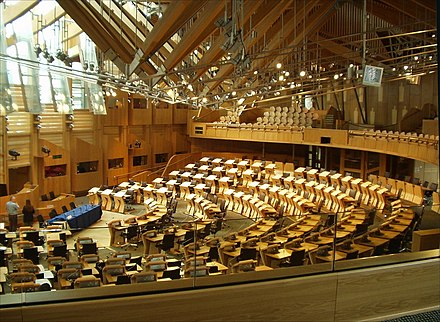 Seating in the debating chamber is arranged in a semicircle, with ministers sitting in the front section of the semicircle, directly opposite the presiding officer and parliamentary clerks. Debating chamber, Scottish Parliament (31-05-2006).jpg