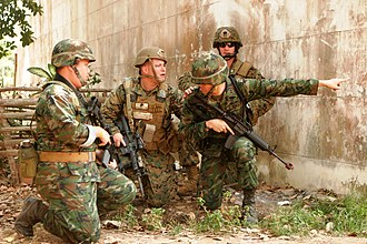 Military history of Thailand - Royal Thai Marines and U.S. Marines discuss how to eliminate hostile forces firing on them from a building during a mock mechanized raid on Feb. 11 2011.