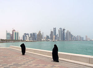 Doha Corniche -  Women walk on Doha Corniche with Doha Skyline in the background