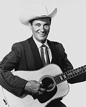 A man wearing a white cowboy hat and dark jacket, smiling broadly while holding a guitar