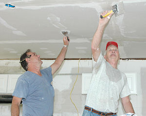 Joint compound - Men apply joint compound to drywall.