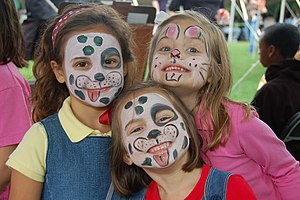 English: Three girls with faces painted as ani...