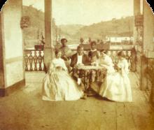 um homem e três mulheres sentados em torno de uma mesa com dois servos de pé no fundo
