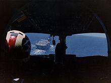 Fotografia degli interni di una cabina di pilotaggio aereo, preso da dietro il pilota, che è seduto sul lato sinistro.  Una portaerei è visibile attraverso il riquadro a sinistra delle finestre pozzetto.