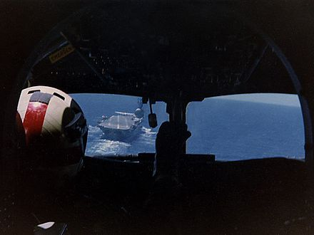 Photograph of the interior of an aircraft cockpit, taken from behind the pilot, who is sitting on the left hand side. An aircraft carrier is visible through the left-hand pane of the cockpit windows.