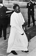 photo noir et blanc d'un homme vêtu d'une soutane blanche, montant des escaliers