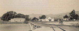 San Simeon, California - Old Hearst pier (built 1878) and the San Simeon waterfront, c. 1890s. Sebastian Store (established 1852,  dark wood) is at center. The white Spanish-style stucco building at right center is a Hearst warehouse, still in use. The ridge in background is the future site of Hearst Castle.