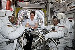 ISS-59 EVA-1 (a) Christina Koch with spacewalkers inside the Quest airlock.jpg