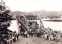 An old photograph showing a crowd of people in the foreground with a steel bridge spanning a river in the background