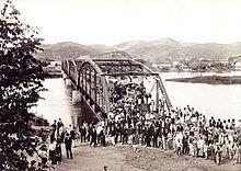 Uma fotografia velha que mostra uma multidão de pessoas em primeiro plano com uma ponte de aço que mede um rio no fundo