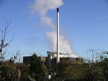 The tops of a row of trees at the foreground obscure a large industrial building. In the centre, reaching to the top, is a white thin chimney and behind this trails white smoke into the sky.