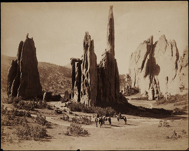 black-and-white photo of a canyon scene, men on horseback to give scale