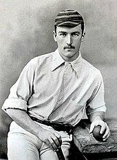 Um homem boliche uma bola de críquete