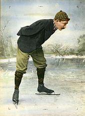 Un homme penché, portant des patins à glace et un bonnet rayé.
