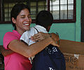 Janina Viteri, left, with the nongovernmental organization Give a Kid a Backpack, hugs a student after giving him a backpack filled with school supplies Aug. 25, 2010, at Hone Creek School in Hone Creek, Costa 100825-M-PC721-004.jpg